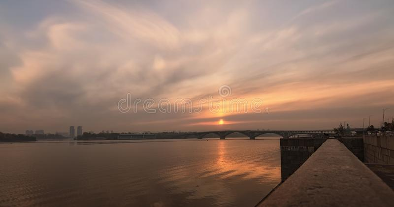 Wide angle landscape panorama of Dnipro River, embankment and Merto Bridge. Colorful vibrant sky reflected in the water stock images