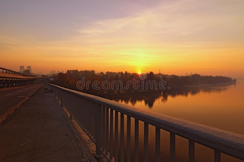 Wide angle landscape panorama of Dnipro River. Magnificent autumn sunrise in Kyiv. Foggy morning landscape. Beautiful city view with rising sun and fiery sky stock photo