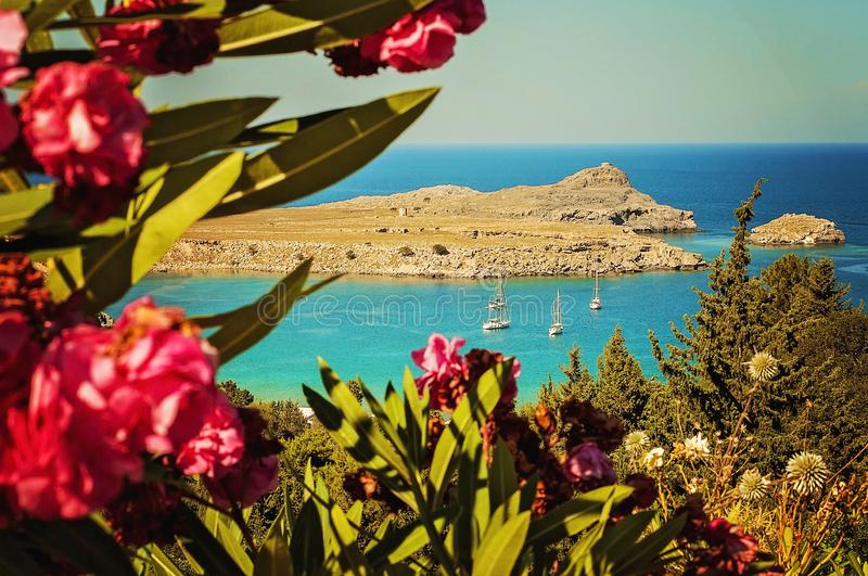 A wide angle landscape view of beautiful Aegean ocean in Greece, Rhodes with red flowers on a foreground and sail boats on the bay stock image