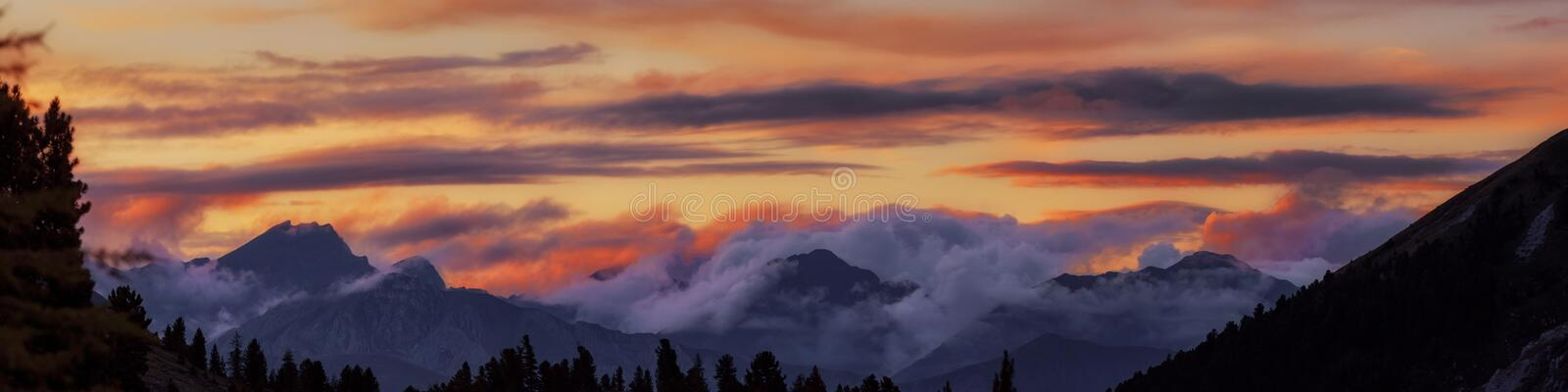 Wide angle panorama silhouette forest and mountain tops in red orange blue clouds gradient sunset stock photos