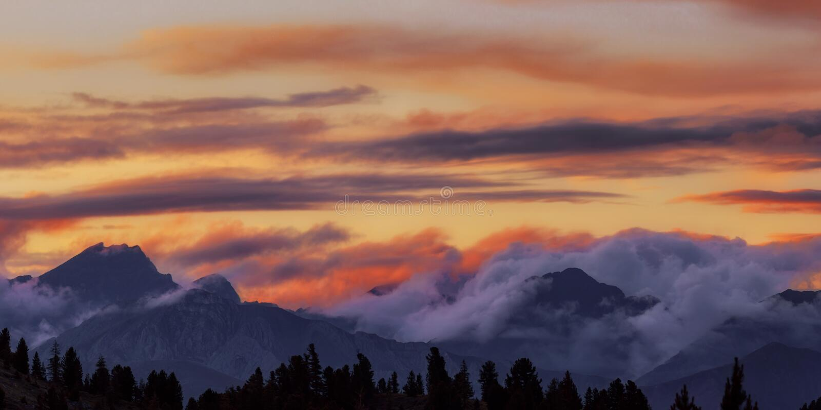 Wide angle panorama silhouette forest and mountain tops in red orange blue clouds gradient sunset royalty free stock photography
