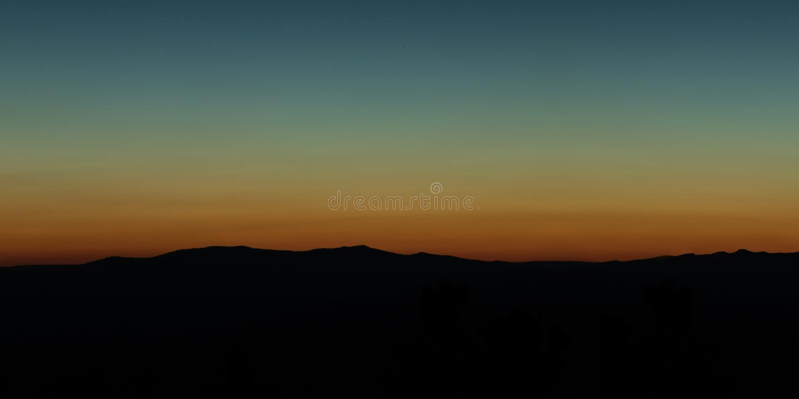 Wide angle panorama silhouette mountain tops in orange blue gradient sunset royalty free stock image