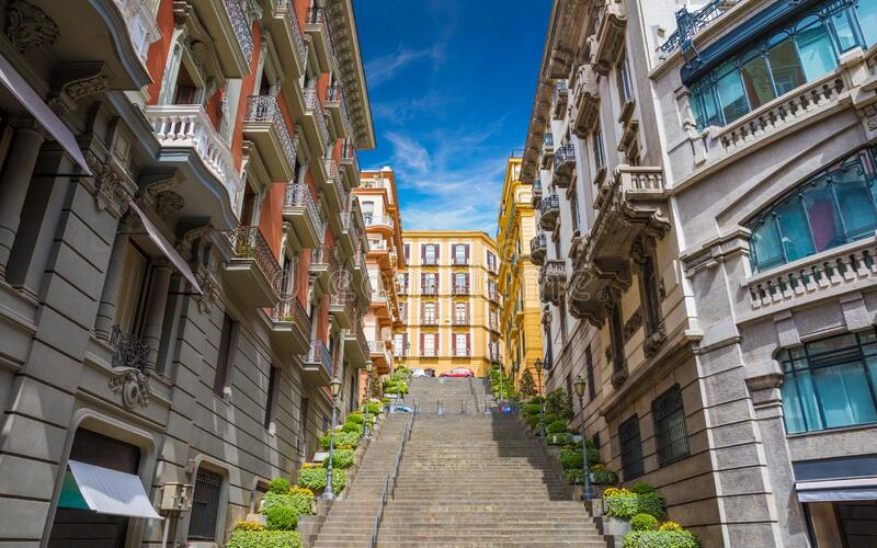 Wide angle photo of italian street with stairs leading up without people in Naples, Italy taken on sunny day royalty free stock image