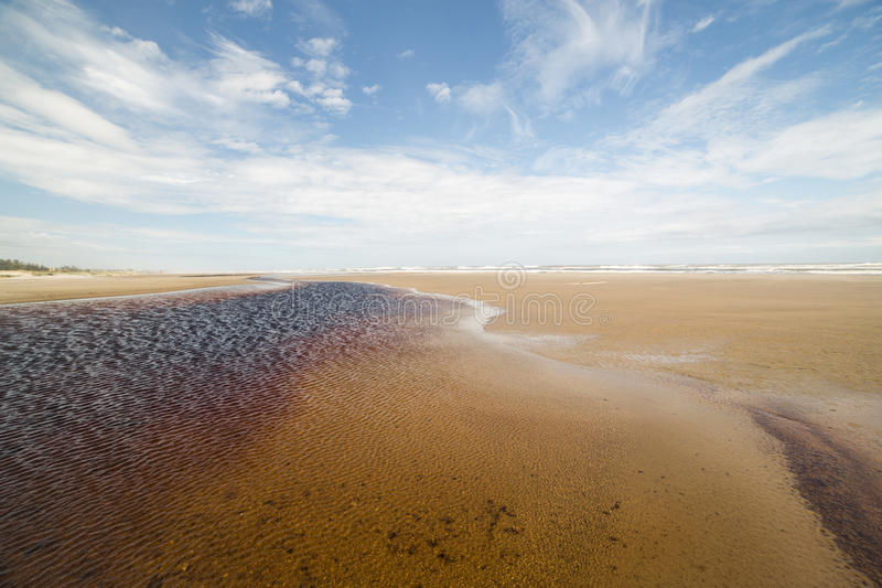 Wide angle rain water lake at the beach with blue sky. Rain water lake formed at the sea shore of a beach and wide angle blue sky and clouds royalty free stock photography