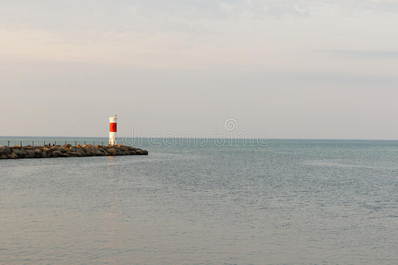 Wide angle Red and white lighthouse. Wide angle view of old red and white lighthouse at sunset on Lake Ontario near Rochester, New York royalty free stock images