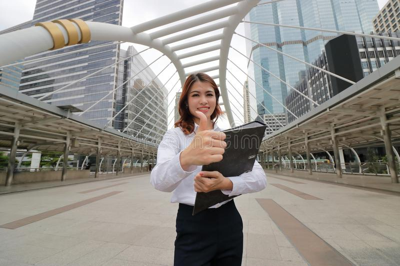 Wide angle shot of cheerful young Asian business woman showing thumb up with document folders on her hand at urban background. stock image