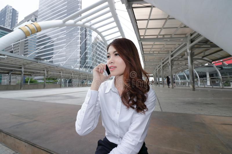 Wide angle shot of cheerful young Asian woman talking on phone at outside office background. Wide angle shot of cheerful young Asian woman talking on phone at royalty free stock image