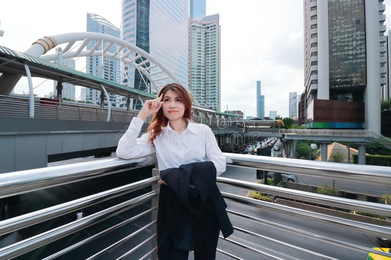 Wide angle shot of confident young Asian business woman thinking to forward at urban city background. Wide angle shot of confident young Asian business woman royalty free stock images