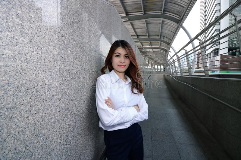 Wide angle shot of confident young Asian businesswoman standing and positive look at walkway in the urban building background. Le. Adership woman concept stock photos