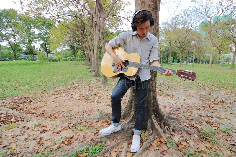 Wide angle shot. Guitarist man with headphones standing and playing acoustic guitar in outdoor park. Wide angle shot. Guitarist man with headphones standing and royalty free stock photography