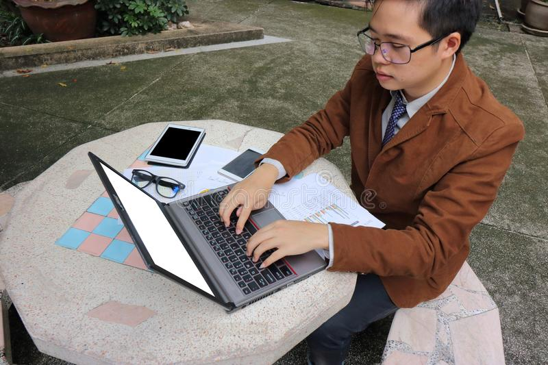 Wide angle shot of handsome yong business man is using laptop with blank screen for his work at outdoor. royalty free stock photos