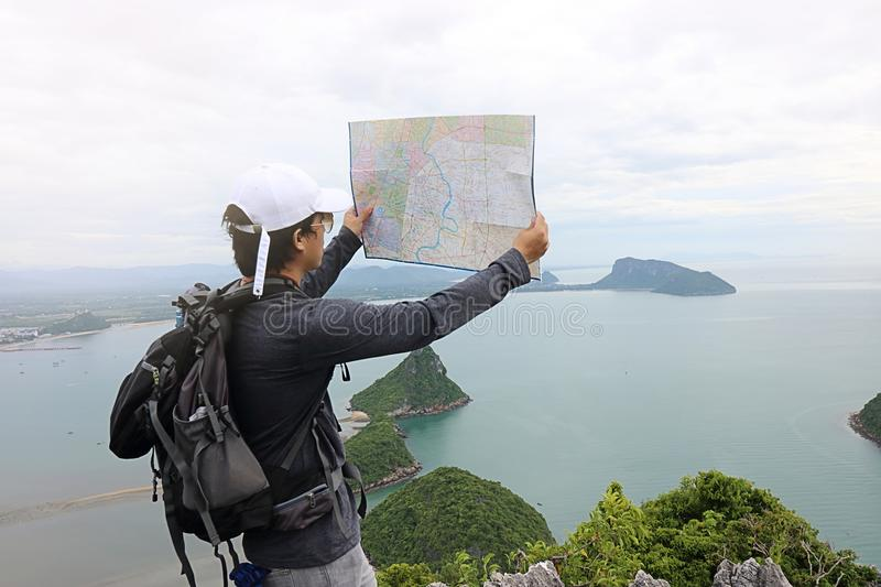 Wide angle shot of hipster young Asian man with backpack standing on the stone and exploring map on the mountain.  royalty free stock photos