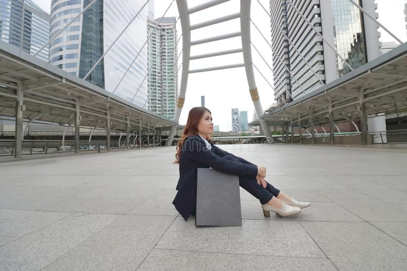 Wide angle shot of pretty face young Asian secretary thinking something and sitting on the floor of walkway at urban building back. Ground stock photo