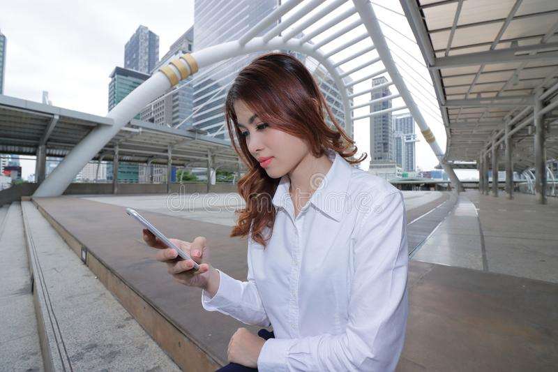 Wide angle shot of pretty young Asian secretary woman using mobile smart phone at walkway outside office. Wide angle shot of pretty young Asian secretary woman stock image