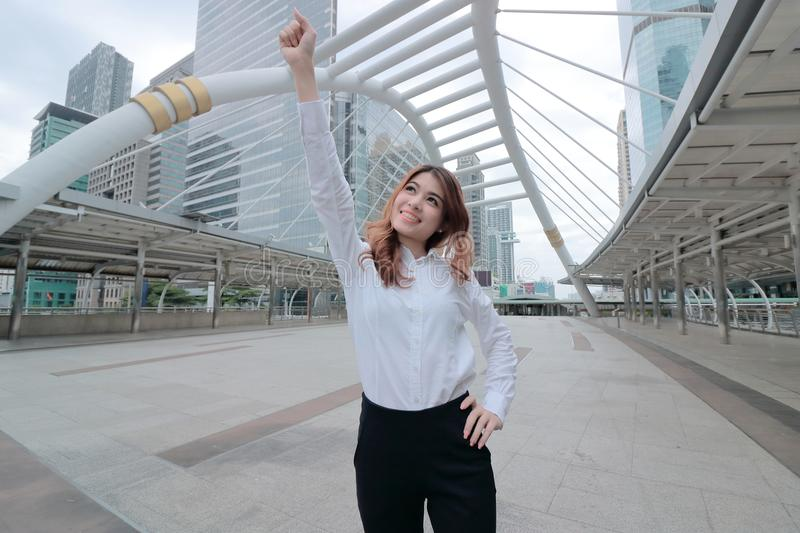 Wide angle shot of successful young Asian business woman raising her hand and smiling at urban building background stock photography