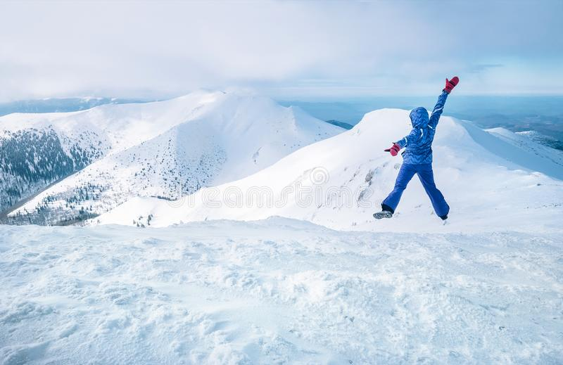Wide angle shot of woman dressed in ski warm clothing jumping on the mountain peak with snowy range and valley on the background. Freedom concept image stock photo