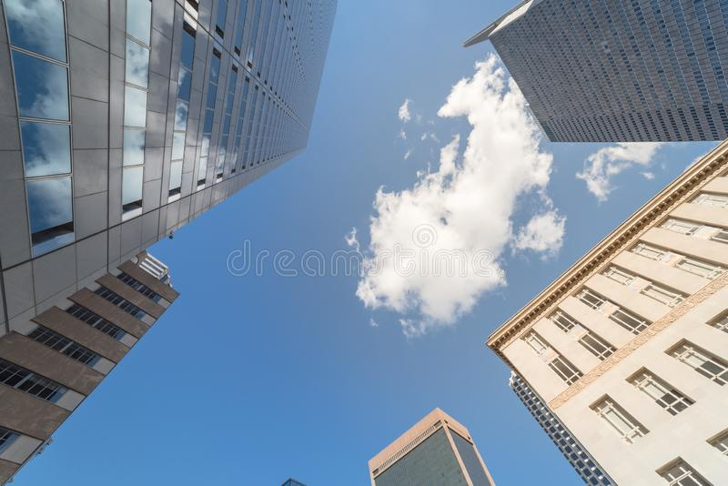 Looking up of skyline buildings in downtown Dallas, Texas, USA c. Wide angle upward view of skyscrapers against cloud blue sky in the business district area of stock photo
