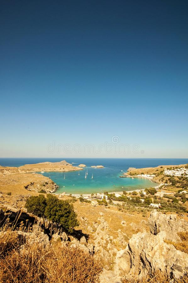 A wide angle vertical landscape view and a shot from a mountain to a little village Lindos in Rhodes, Greece and there`s sail. A wide angle vertical landscape stock photos