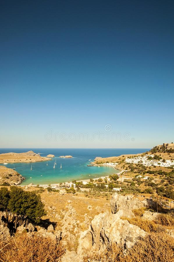 A wide angle vertical landscape view and a shot from a mountain to a little village Lindos in Rhodes, Greece and there`s sail boat. A wide angle vertical stock images