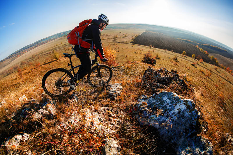 Wide angle view of a cyclist riding a bike on a nature trail in the mountains. stock photography