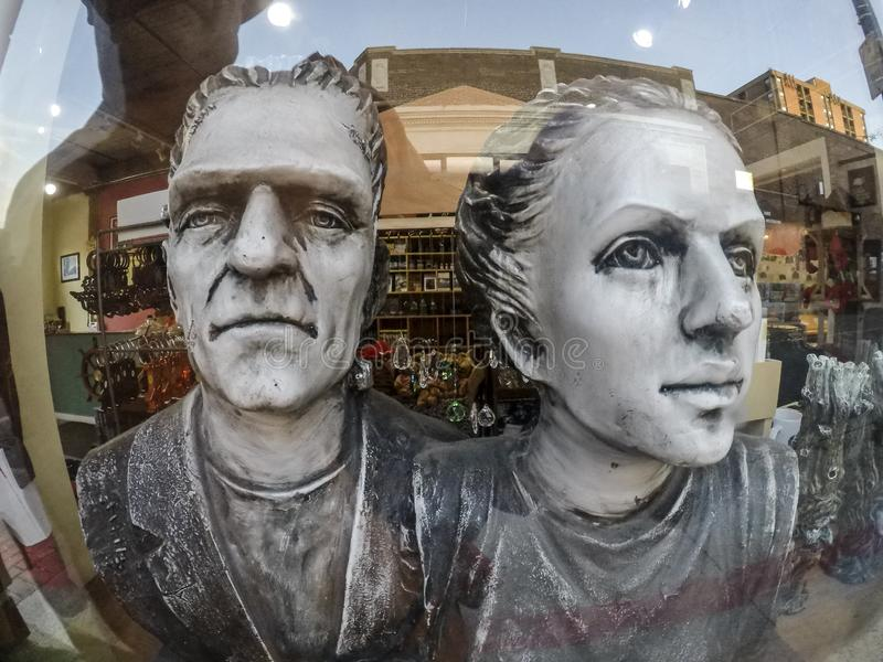 Wide angle view of faces of souvenir statuettes in store window. In Salem Massachusetts stock photography