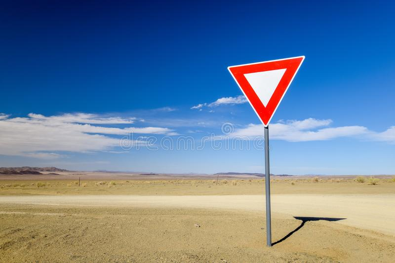 Wide angle view of a give way yield sign at a gravel road intersection in the Namibian Desert between Ai-Ais Fish River Canyon a. Nd Aussenkehr. Mountains in the royalty free stock photos