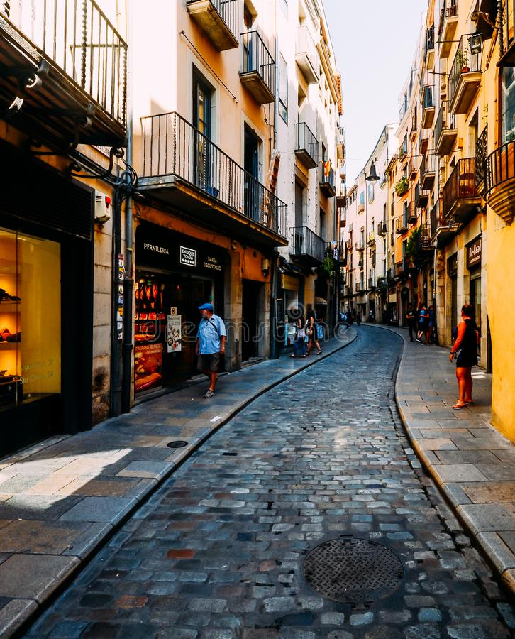 Wide angle view of narrow cobblestone street in the historic centre of Girona royalty free stock photo