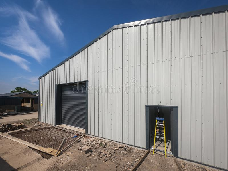 Wide angle view of the outside of a warehouse on a backdrop of blue sky. stock images