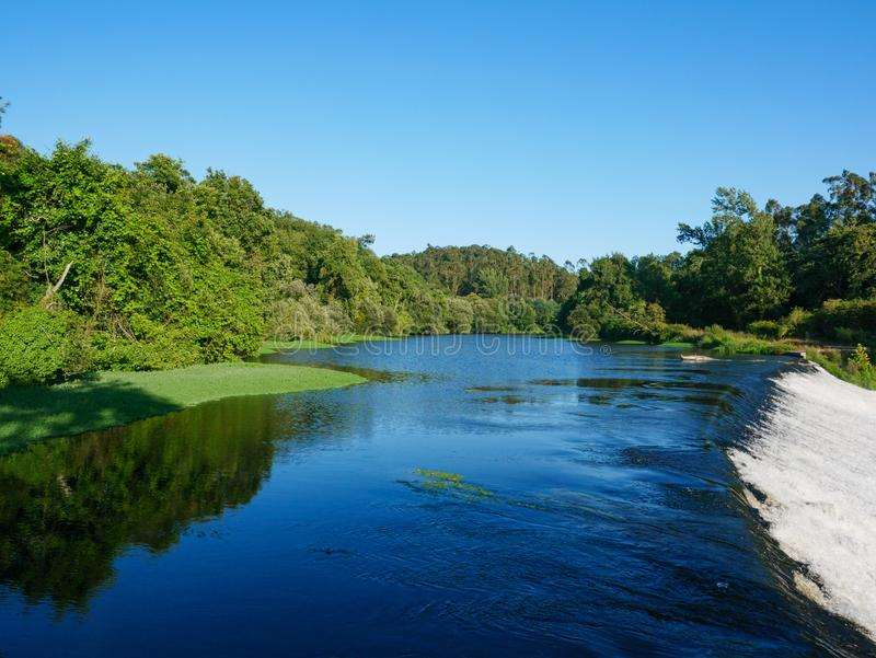 Wide angle view over Ave River in Touginho, Vila do Conde, Portugal. On bright sunny summer day with blue sky. Fast flowing water over dam in foreground and royalty free stock photography