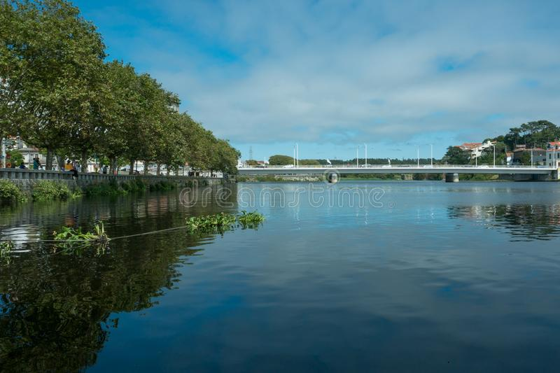 Wide angle view over River Ave in Vila do Conde, Portugal on a bright summer day. With blue sky and green trees lining bank royalty free stock photography