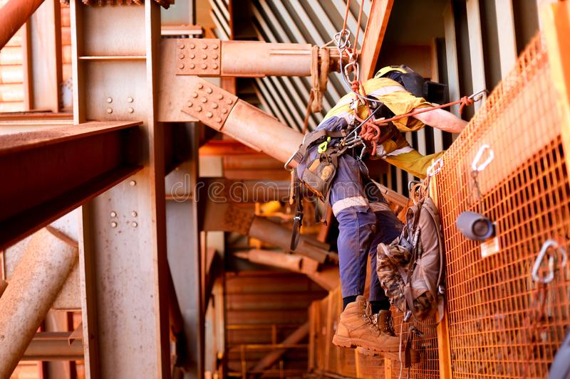 Wide angle view picture of male rope access welder worker wearing full safety harness, helmet working hanging on tie line setting royalty free stock photography