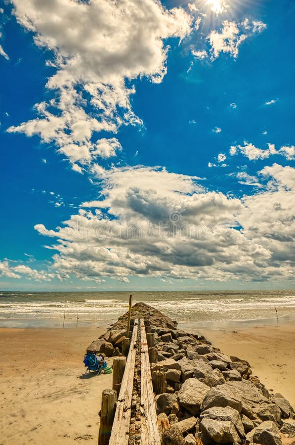 A wide angle view of a rock wall jutting into the ocean. royalty free stock photography