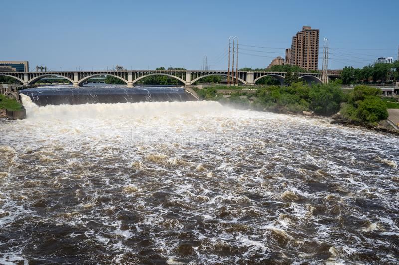 Wide angle view of St. Anthony Falls in downtown Minneapolis, Central Avenue Bridge in background. Fast currents create foamy stock image