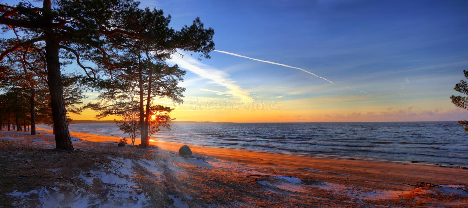 Wide-angle view of the sunset on the Gulf of Finland. Large-format panorama of late sunset on the Gulf of Finland with the first snow stock image