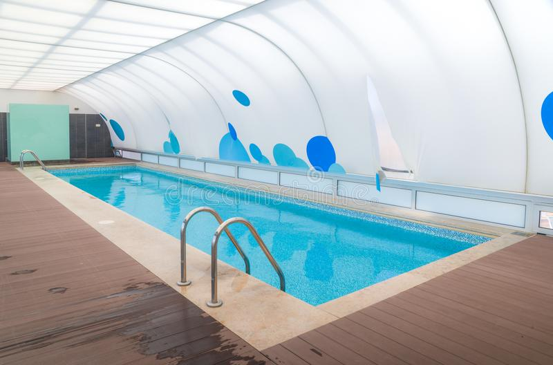 Wide angle view of swimming pool with a roof.  royalty free stock photo