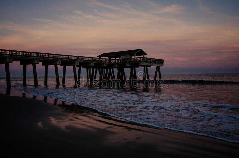 Wide angle view of the Tybee Island Pier in Georgia. Colorful sunset with pinks and purple colors in the sky stock photography