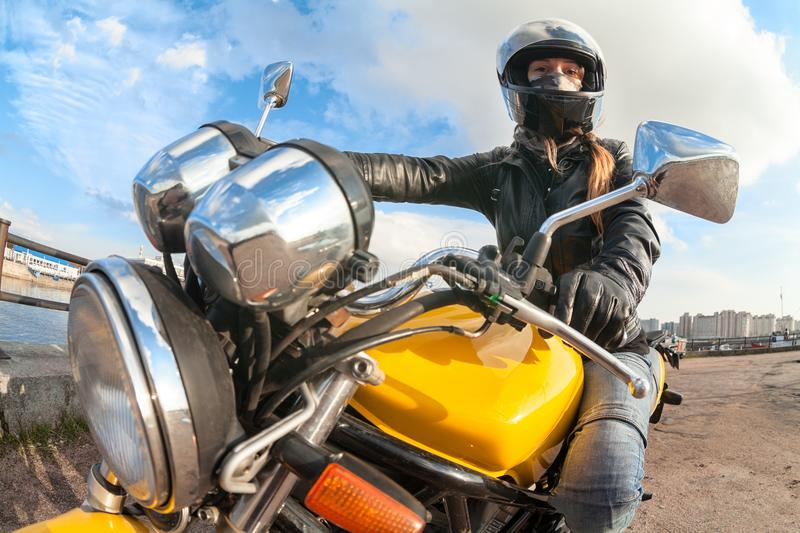 Wide angle view at young woman motorcyclist sitting on bike, focus on girl royalty free stock photography