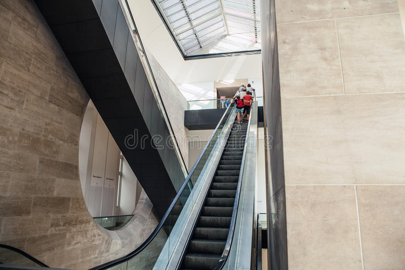 Wide angled view to perspective escalators stairway. PARIS, FRANCE - AUGUST 30, 2015: Wide angled view to perspective escalators stairway. Louvre indoor. Paris royalty free stock image