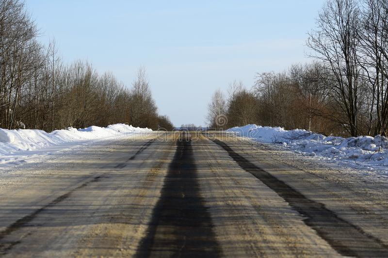 Wide asphalt road, on which there are ruts from cars on the roadway.  royalty free stock photo