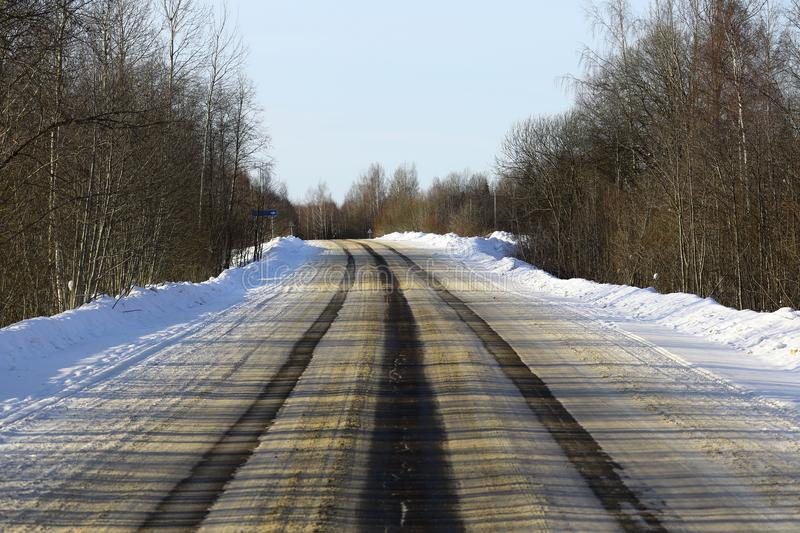 Wide asphalt road, on which there are ruts from cars on the roadway.  stock photography