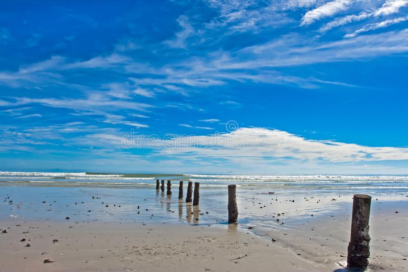 Wide beach with row of posts royalty free stock images