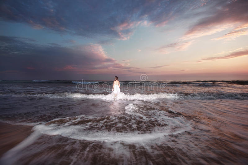 Wide beach scene. Wide angle photo of a girl standing alone in the water stock images