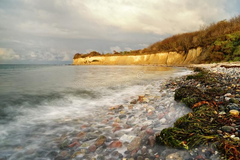 Wide beach with seaweed and stones in the evening light, water movement. Wide beach with seaweed and stones in the evening light, overlooking the water and the stock photo