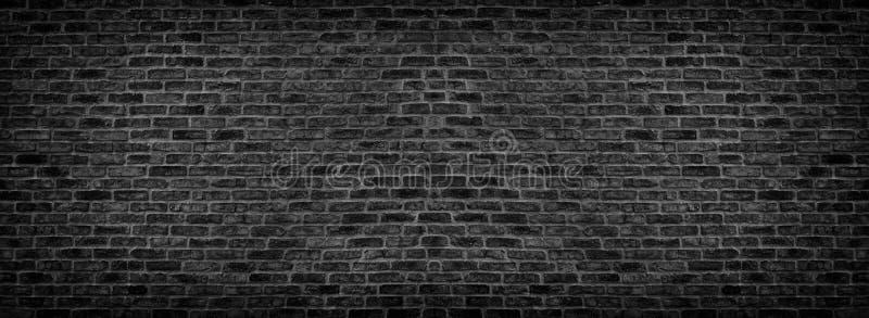 Wide black brick wall texture. Rough brickwork panorama. Dark panoramic background royalty free stock photography