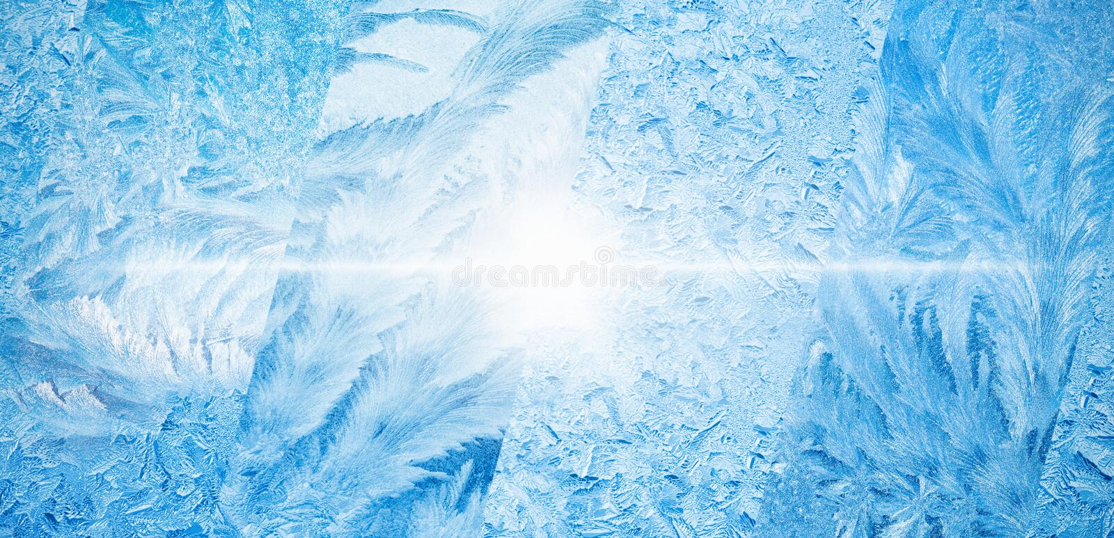 Wide blue winter background, collage of frozen icy windows. Cold sunny weather, bright sun shines through frozen window, weather forecast concept stock images