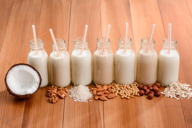 Wide choice of vegan milk. Row of bottles of homemade drinks made of nuts, cereal and soy beans stock images