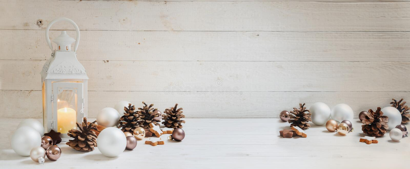 Wide christmas background with a candle light lantern, baubles, royalty free stock photo