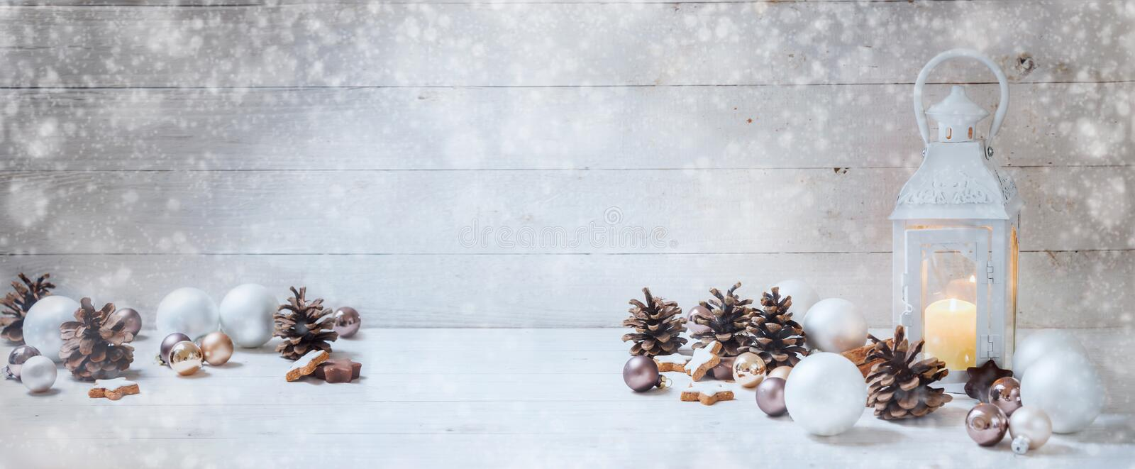 Wide christmas background with a candle light lantern, baubles,. Cinnamon stars, cones and snoe on rustic bright wood, panorama format for website banner, copy