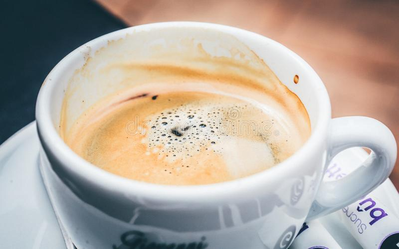 Wide closeup shot of hot creamy coffee in a white ceramic cup. A wide closeup shot of hot creamy coffee in a white ceramic cup royalty free stock photo
