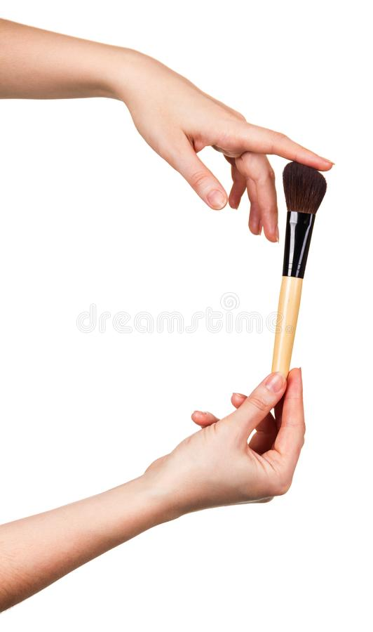 Wide cosmetic brush for applying makeup Foundation in woman hands isolated on white stock photo